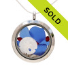 Genuine blue beach found sea glass is combined with crystal ruby gemstones, a real sandollar and beach sand in this silver stainless steel locket necklace.
