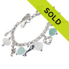 Genuine Sea Glass Bracelet. Amazing pale aqua and whitish real sea glass pieces from England  are combined with solid sterling charms on a fully soldered bracelet. Charms include lighthouse, parrot,lifesaver,lobster,manatee and 2 flip flops.