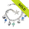 A stunning combo of vivid and medium blue real sea glass pieces combined with solid sterling charms on a fully soldered sea glass bracelet. Solid Sterling Charms include three different shells, a sand pail with seperate shovel, a sandollar and two starfish.