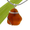 A nice piece of genuine ridged sea glass in amber brown and a simple secure  wire wrapped sterling setting.