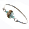Two pieces of beach found sea glass in bright aqua on this solid sterling silver half round sea glass bangle bracelet. The center bead is handmade by a glass artist and resembles the ocean.