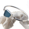 Beautiful vivid gray blue sea glass ( with crizzle) bracelet set in fine and sterling silver on a silver round bangle.