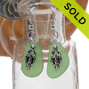A simple pair of genuine green sea glass earrings with sterling lobster charms in a lightweight simple setting.