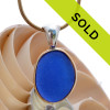 A small round piece of rich cobalt blue sea glass set in our classic and elegant Tiffany Deluxe Wire Bezel setting in a mixture of gold and silver. This setting leaves the sea glass piece totally UNALTERED from the way it was found on the beach. Sorry this sea glass necklace pendant has been sold!