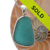 A really neat almost perfectly flat but thick piece of VIVID Teal sea glass set in our Deluxe Wire Bezel© necklace pendant setting. Sorry this sea glass necklace pendant is no longer available.