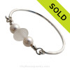 A thick piece of very round piece of white English Seaham Sea Glass combined with genuine fresh water pearls on a solid sterling bangle bracelet. Sorry this Sea Glass Bracelet has been SOLD!