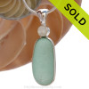 Along piece of top quality aqua English sea glass pendant set with a round mother of pearl in a tube bezel setting. Sorry this piece of Sea Glass Jewelry has been SOLD!