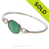 Genuine  Vivid Aqua Green Sea Glass Bangle Bracelet set in our Deluxe Wire Bezel© sterling silver setting. Sorry this piece of Sea Glass Jewelry is no longer for sale.