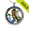 """A beautiful sliver of natural light and dark blue sea glass combined in a stainless steel locket necklace a two real starfish and beach sand. A seafan and bit of """"seaweed"""" makes this a great choice for any ocean lover!  This a great gift, specially for those with a September Birthday SOLD - Sorry this Sea Glass Jewelry selection is NO LONGER AVAILABLE!"""