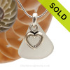 A  perfect piece of pale green genuine sea glass with a solid sterling bail and detailed heart charm.