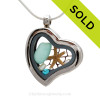 Beautiful piece aqua sea glass pieces combined with a real starfish. Finished with freshwater pearls in this heart locket.