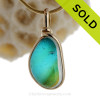 This is a stunning piece of End Of Day Sea glass in electric teal mixed with a vivid green and slash of gold is set in our Original Wire Bezel© setting in gold.