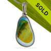 A Lovely Petite Mixed  Bright Spring Green and a touch of Blues multi sea glass set in Sold Sterling Silver Deluxe Wire Bezel© pendant setting.