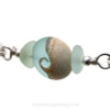 A detail of the top quality genuine sea glass pieces and the lovely handmade light blue wave bead.
