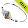 Genuine White Sea Glass Bangle Bracelet set with a handmade lamp work glass wave bead in storm blue with sterling end beads on a solid sterling half round premium bangle bracelet.