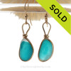 SUPER ULTRA RARE Mixed Electric Aqua Sea Glass Earrings set in our Original Wire Bezel© setting In 14K Goldfilled. This setting leaves the sea glass totally UNALTERED from the way it was found on the beach letting these amazing rare sea glass pieces really shine!  Painstakingly matched for unaltered beach found sea glass pieces from Seaham England and the site of Victorian art glass factories. A once in a lifetime pair of Seaham Sea Glass Earrings in gold .