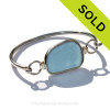 A lovely oblong piece of Stormy Gray Blue Flat Sea Glass Bangle Bracelet set in our Deluxe Wire Bezel© Sterling Silver Setting. SOLD - Sorry This Sea Glass Jewelry Item is NO LONGER AVAILABLE!