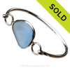 A lovely oblong piece of Bright Carolina Blue Sea Glass Bangle Bracelet set in our Deluxe Wire Bezel© Sterling Silver Setting. SOLD - Sorry This Sea Glass Jewelry Item is NO LONGER AVAILABLE!