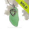Green genuine sea glass with a solid sterling bail and detailed heart in hearts charm.