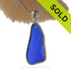 A long slice of Lovely and Tactile Cobalt Blue Beach Found Sea Glass In Solid Sterling Silver Deluxe Wire Bezel© Necklace Pendant. This Setting that leaves the sea glass piece just the way it was found on the beach and combines our original deluxe wire setting taken to the to the next level by incorporating a Solid Sterling cast bail.