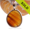 A stunning vibrant streaked golden amber piece of sea glass set in our Deluxe Wire Bezel setting in Solid Sterling Silver.