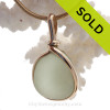 Almost perfectly round Peridot natural sea glass piece set in our Original Wire Bezel setting in 14K Rolled Gold setting.