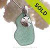 An organic shaped piece of aqua green sea glass set on a Solid Sterling cast bail and finished with a solid sterling silver sandollar charm.