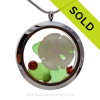 Green sea glass and a real sandollar and beach make this a great locket necklace for the holidays. Ruby Red  & Emerald Green crystal gems finish the locket with some extra bling.