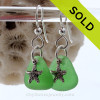 Green Genuine Sea glass earrings in sterling with sterling starfish charms These are done in a simple drilled setting to let these true sea glass gems. Details of solid sterling starfish charms these earrings for a polished professional and beachy look.
