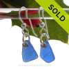 A pair of natural frosted surf tumbled sea glass earrings in a lucky cobalt blue on sterling fish hooks.