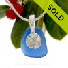 Nice blue beach found sea glass combined with a solid sterling sandollar charm and presented on a solid Sterling silver snake chain.
