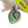 Stunning glowing Tropical Aqua Green genuine sea glass with a solid sterling bail and detailed heart in hearts charm.
