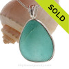A STUNNING HUGE piece of Bright Aqua Certified Genuine Sea Glass Pendant in our Deluxe Wire Bezel© setting in Sterling Silver. Perfect TOP QUALITY sea glass in a setting that leaves both front and back open and leaves the glass unaltered from the way it was picked off the beach. It is a very thick perfectly frosted piece that seems to hold and trap the light inside.