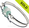 A thick almost perfectly round pure white sea glass piece combined with 2 frosted aqua glass beads and  set on our half round solid sterling silver bangle bracelet!