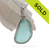 A lovely piece of beach found glass from Seaham England in a stunning aqua blue is set in our Original Wire Bezel© pendant setting.