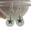 Natural pale seafoam green sea glass earrings are set with solid sterling  starfish charms and are presented on sterling silver fishook earrings.