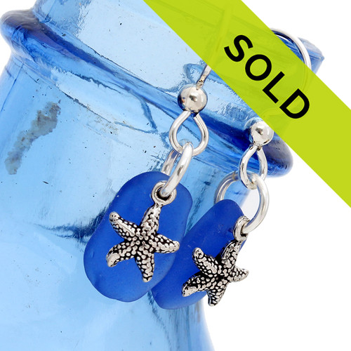 Genuine Blue Sea Glass On Silver Earrings W/ Starfish Charms  Our sea charmed earrings feature sea life charms. This pair is a natural cobalt blue sea glass with solid sterling starfish. The pair comes on professional grade ear wires (SHOWN). Sorry these earrings has SOLD!