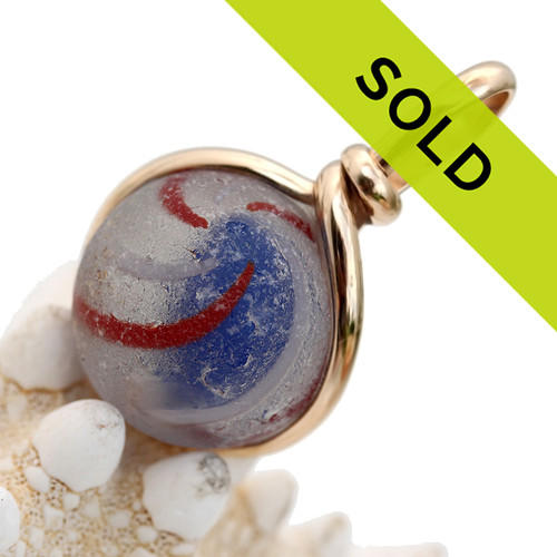 """A red white and blue Onion Skin sea glass marble is expertly set in our Original Wire Bezel© setting. A great top quality sea glass marble, you can see the characteristic """"C""""'s of genuine sea glass."""