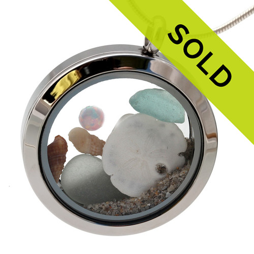 SORRY THIS LOCKET HAS SOLD! Genuine fire opal combined with seafoam and aqua sea glass and topped off with a real sandollar, shells and beach sand. A great locket for anyone, specially those with an October birthday. Opal is one of the October Birthday gemstones. This is an authentic fire opal from Australia.