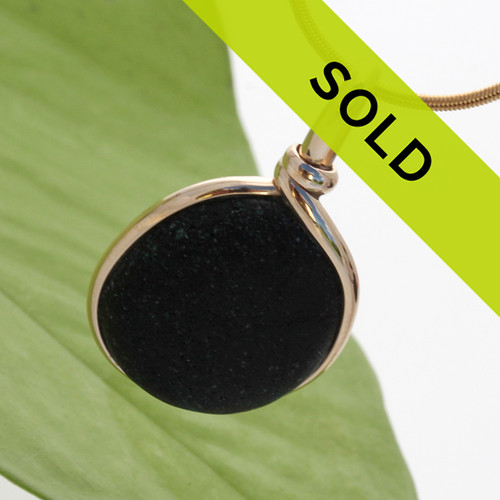 """This """"ALMOST"""" black sea glass piece is set in our Original Wire Bezel© pendant setting. An amazing piece of sea glass from the UK that originated as scrap or slag glass."""