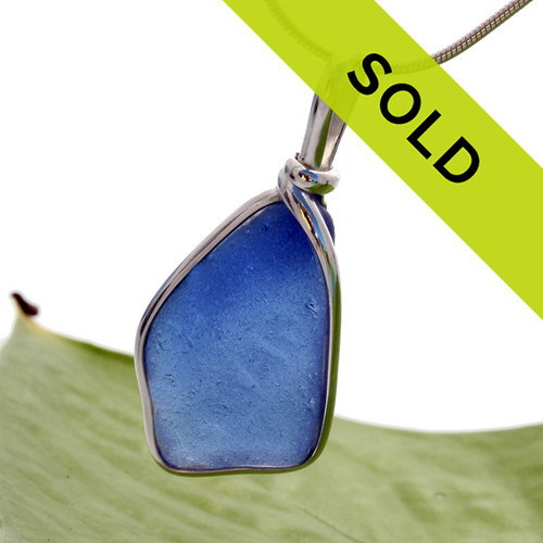 """An embossed blue sea glass piece set in our Original Wire Bezel© pendant setting. A neat piece of sea glass with distinct embossing from it's origin as a Milk Of Magnesia bottle. The letters """"MAD"""" originally said Made In The USA and were embossed on the bottoms of the bottles. Sorry this sea glass pendant has SOLD"""