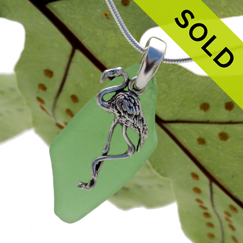 A long piece of green sea glass is combined with a handcast solid sterling bail and finished with a silver flamingo charm. Sorry this sea glass jewelry piece has been SOLD!