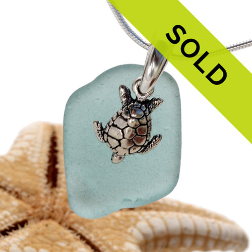 Beach found aqua blue sea glass is combined with a handcast solid sterling bail and finished with a sterling silver sea turtle charm.