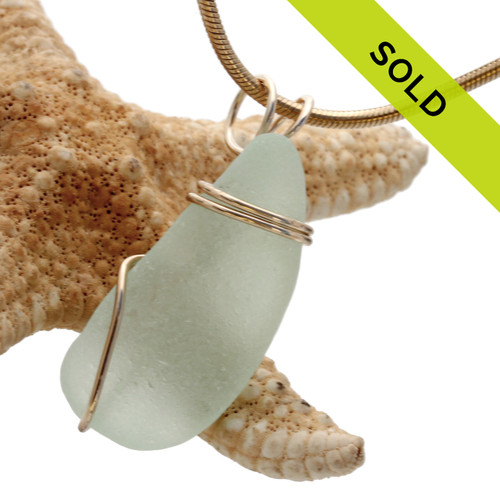 A perfect seafoam green sea glass piece set in our basic beach wire wrap in gold. This setting leaves the sea glass totally unaltered from the way it was found on the beach.
