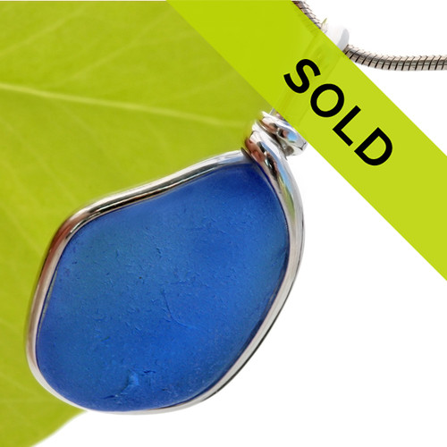 A medium vivid blue sea glass piece set in our Original Wire Bezel© pendant setting.