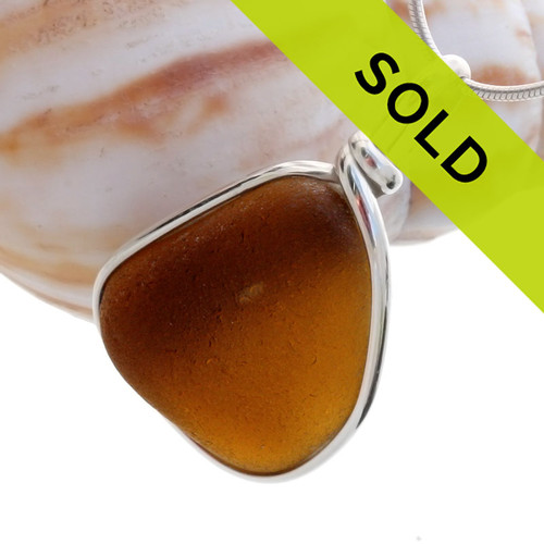 A rich brown sea glass piece set in our Original Wire Bezel© setting. This sea glass is left just the way it was found in the beach, securely set in our signature sterling setting.