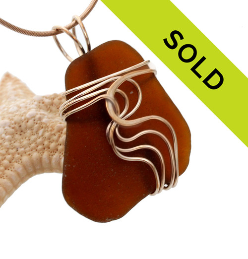 A  TOP quality piece of brown sea glass set in our signature WAVES pendant setting. This setting leaves the sea glass totally open so you can reach up and feel the amazing tactile texture of this genuine sea glass piece. Sorry this piece has been sold!