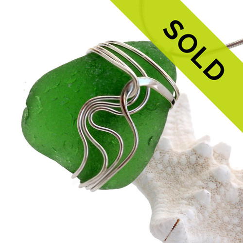 A large thick chunky piece of frosty green sea glass set in our signature Squiggles© pendant setting in sterling silver.