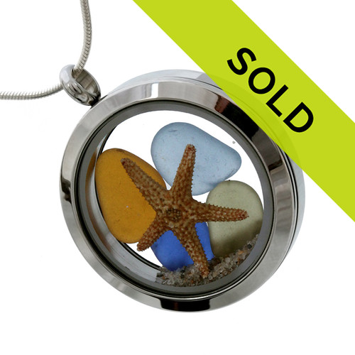 Sea glass in jeweltone colors of green, amber and blue combined with a real starfish and beach sand in this one of a kind stainless steel locket necklace. Sorry this locket has sold!