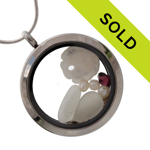 Pure white genuine sea glass pieces combined with a real sandollar and an Amethyst (February Birthstone) or Alexandrite (June Birthstone) color gemstone and pearls (also June Birthstone) in a stainless steel locket.